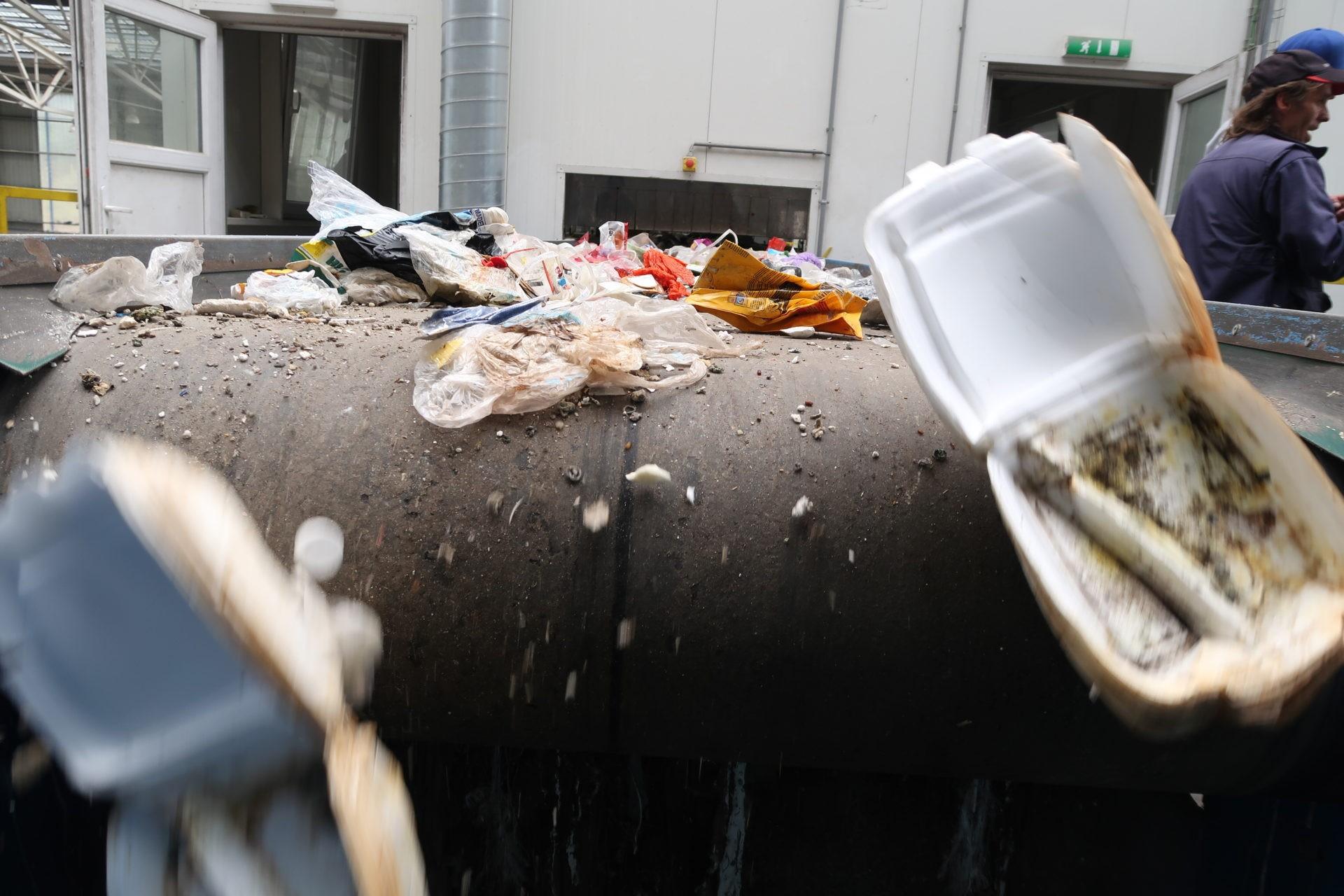 """Z haly putuje plastový odpad povyčištění odnečistot a""""hrubém"""" dotřídění dopravníkovým pásem do""""věže"""" ktzv.ručnímu dotřídění, kdejedotříděn podle komodit - tyodkládají pracovníci třídičky podle druhu dospeciálních nádob. Vtéto třídičce propadá roztříděný odpad podle druhu pozmáčknutí páky doobrovských kójí, pytlů čikontejnerů. PETláhve ještě musí projít tzv.perforátorem, kterýjepropíchne anásledně jsou lisovány dobalíků."""